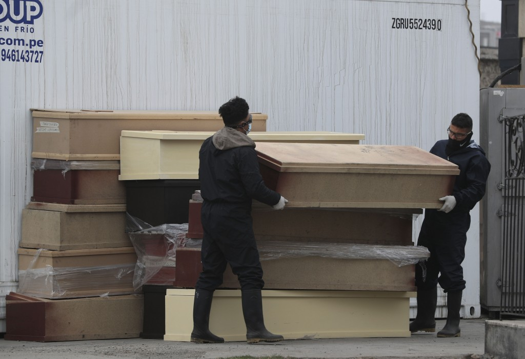 Funeral workers lift a coffin containing a body to be taken to the crematorium at El Angel cemetery in the section dedicated to COVID-19 victims in Li...