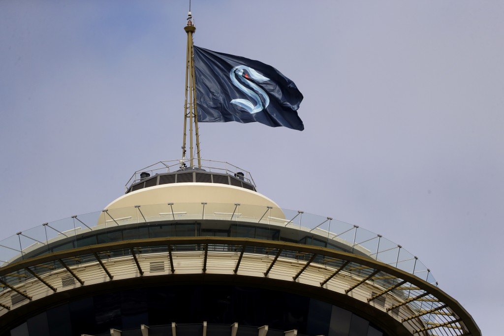 A flag with the new logo for the newly-named Seattle NHL team, the Seattle Kraken, flies atop the iconic Space Needle Thursday, July 23, 2020, in Seat...