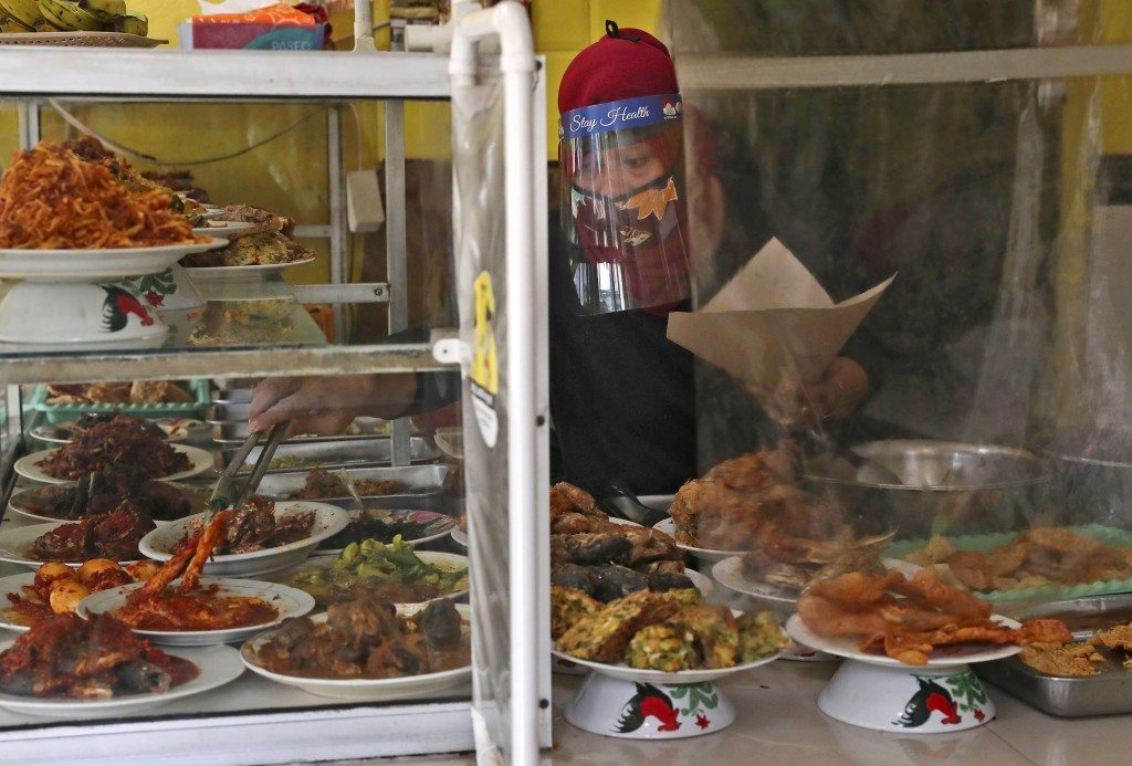 An employee serves customers from behind a plastic sheet installed as a precaution against the new coronavirus at a street food stall in Jakarta, Indo...
