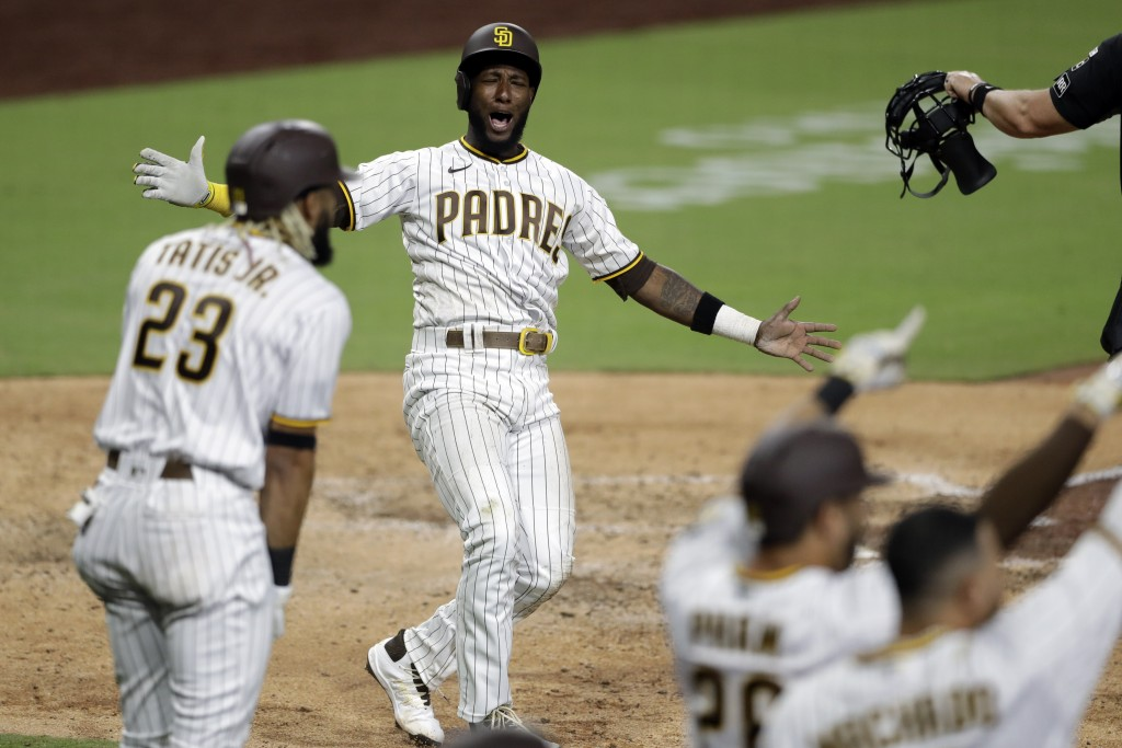 San Diego Padres' Jurickson Profar, second from left, celebrates after scoring off a three-RBI double by Eric Hosmer during the seventh inning of a ba...