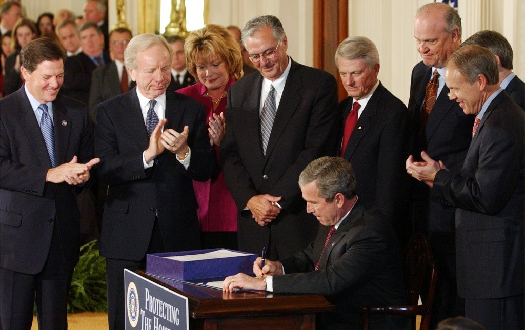 FILE - In this Monday, Nov. 25, 2002 file photo, President Geroge W. Bush signs legislation creating the Department of Homeland Security, during a cer...