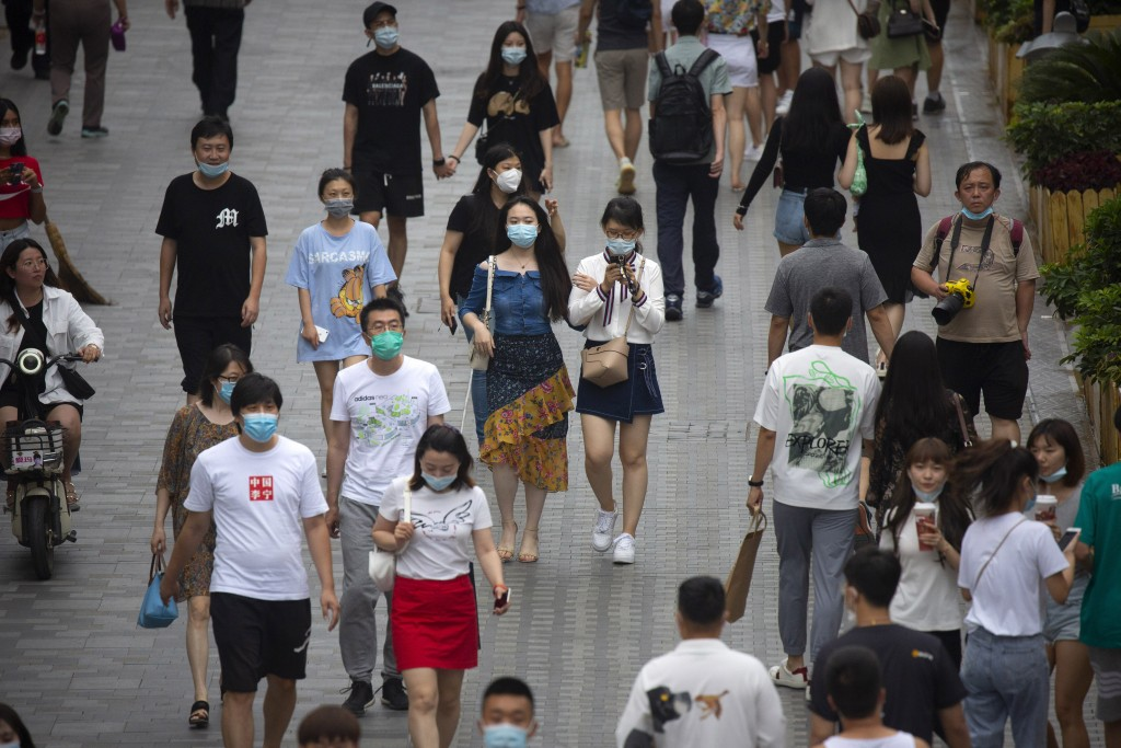 People wearing face masks to protect against the coronavirus walk through an outdoor shopping area in Beijing, Saturday, July 25, 2020. China on Satur...