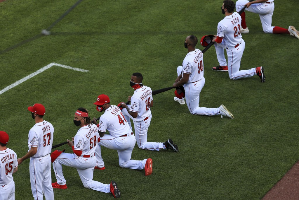 Cincinnati Reds' Luis Castillo (58), Pedro Strop (46), Raisel Iglesias (26), Amir Garrett (50) and Cody Reed (23) take a knee prior to a baseball game...