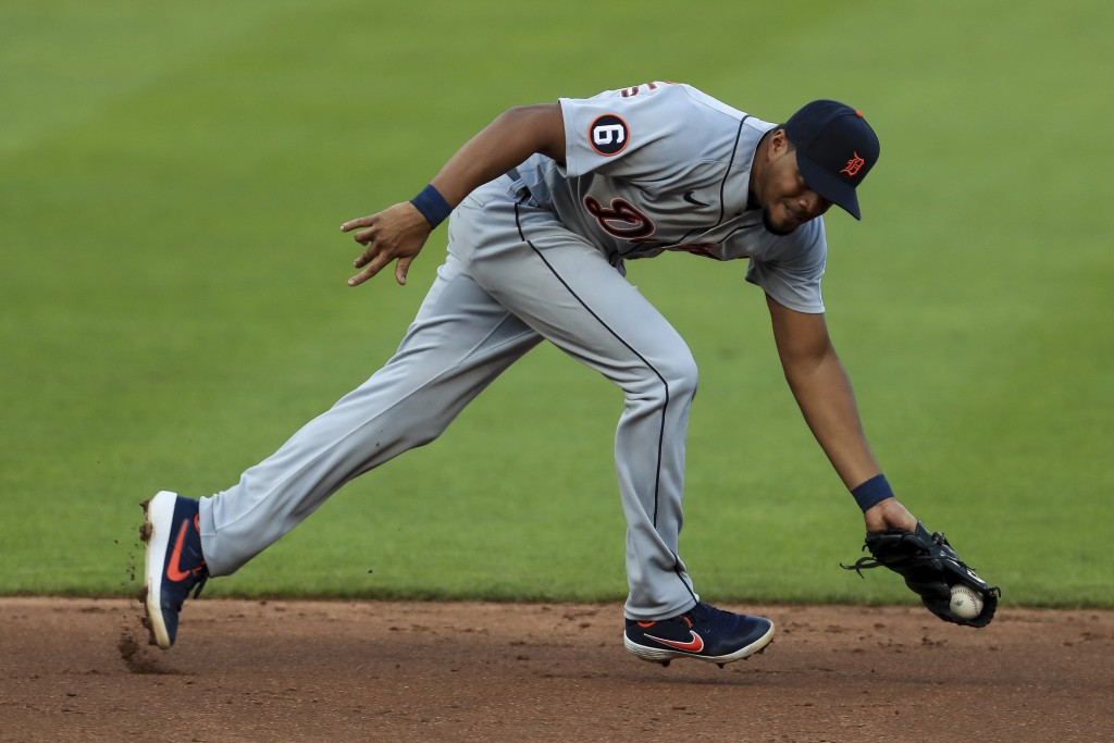 Detroit Tigers' Jeimer Candelario fields the ball before throwing out Cincinnati Reds' Eugenio Suarez in the third inning during a baseball game at Gr...