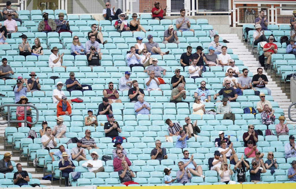 Spectators observe social distancing in the stands during the friendly cricket match at the Oval, London, Sunday, July 26, 2020. Spectators have been ...