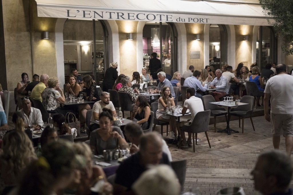A couple sits for dinner at a crowded restaurant in Marseille's Old Port, southern France, Saturday, July 25, 2020. France is reporting a sharp uptick...