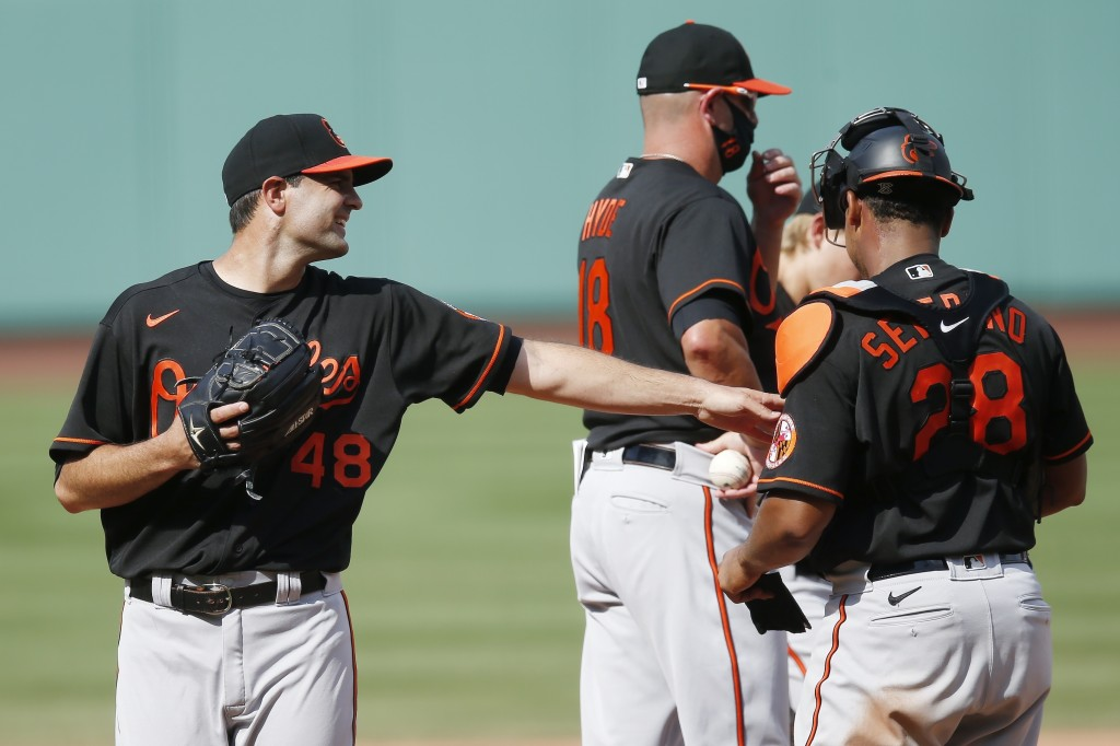 Baltimore Orioles' Richard Bleier (48) walks off the mound and reaches out to Pedro Severino (28) after being relieved by manager Brandon Hyde (18) du...