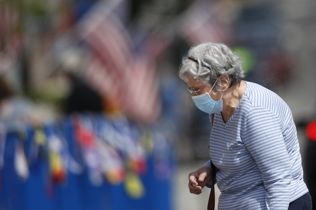A woman wears a mask to protect against coronavirus walking in downtown Bayth, Maine, Saturday, July 25, 2020. (AP Photo/Robert F. Bukaty)