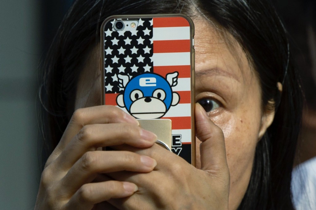 A woman takes a photo with a phone that has a United States flag themed cover outside the United States Consulate in Chengdu in southwest China's Sich...