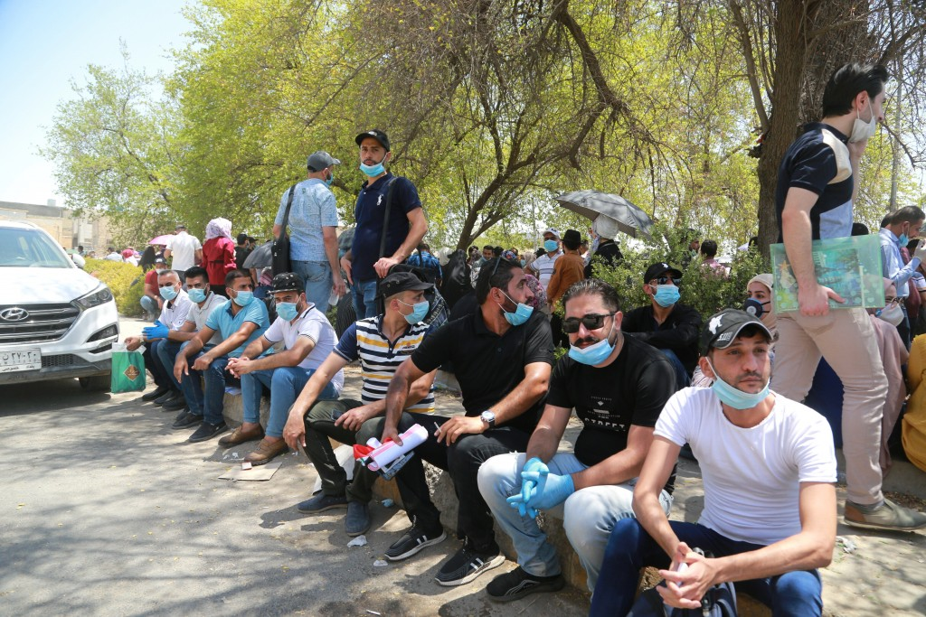 Jobless graduates gather in front of the Ministry of Oil to demand jobs in Baghdad, Iraq, Monday, July 20, 2020. In the Mideast, wave after wave of wa...