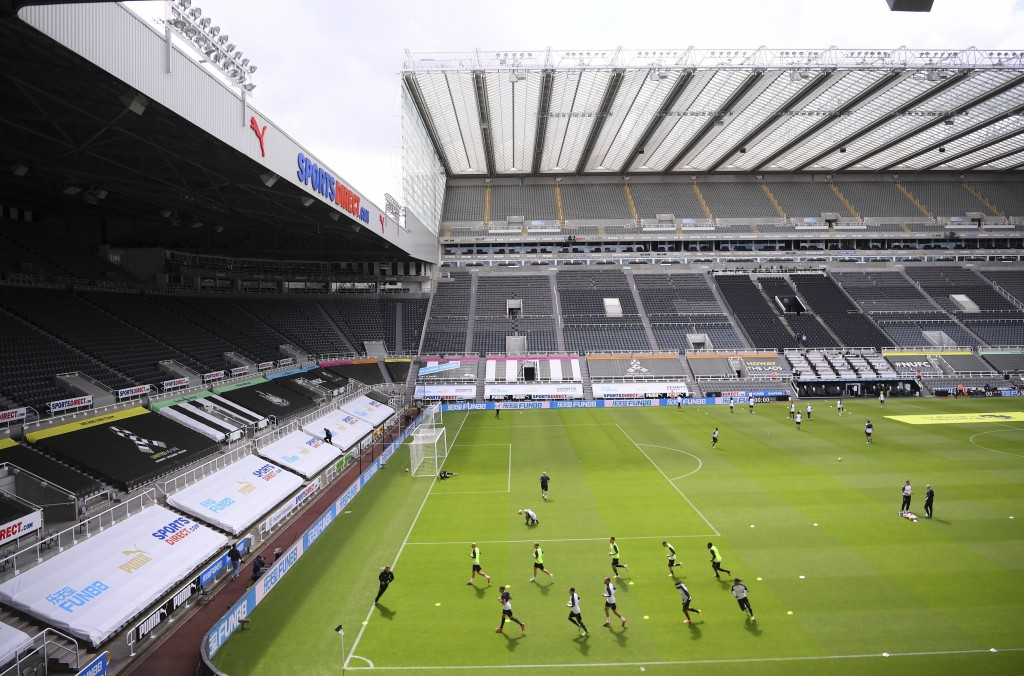 Players warm up before the English Premier League soccer match between Newcastle and Liverpool at St. James' Park in Newcastle, England, Sunday, July ...
