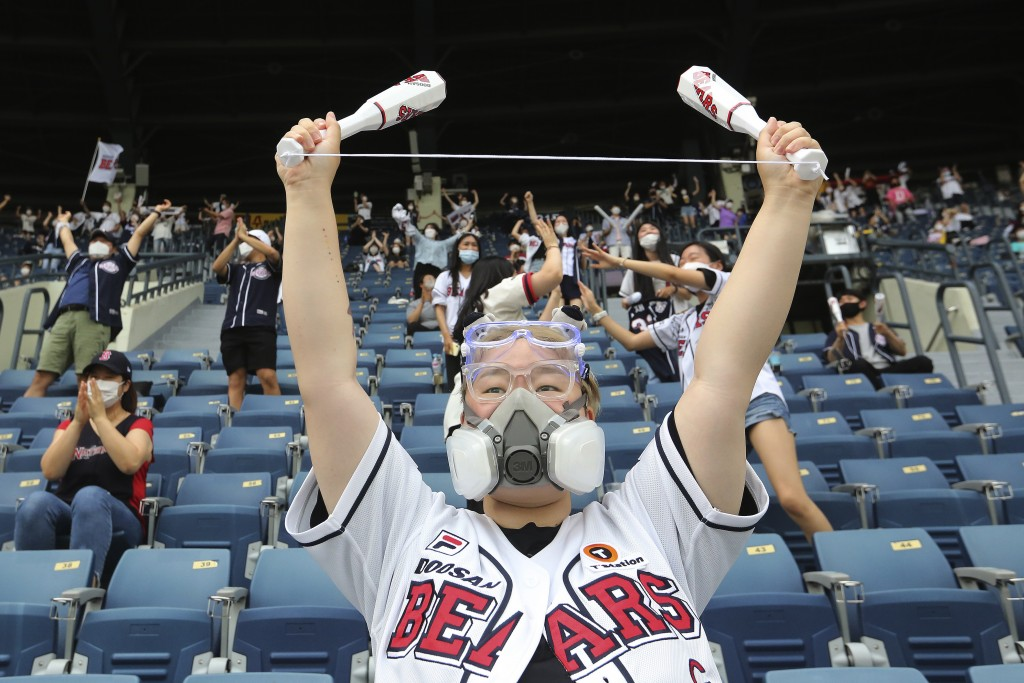 A fan wearing a face masks to help protect against the spread of the new coronavirus cheers during the KBO league game between Doosan Bears and LG Twi...