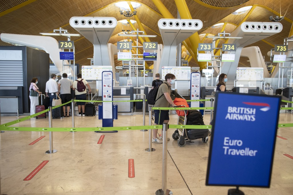 Passengers wearing face masks to prevent the spread of coronavirus queue prior to departure to London at a British Airways check-in desk at Adolfo Sua...