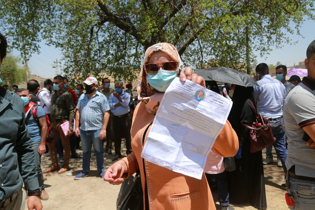 Rowaida Abdul Rahman shows her science master's degree certificate while jobless graduates gather in front of the Ministry of Oil to demand jobs in Ba...