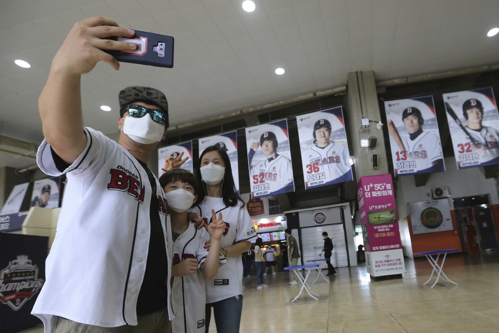 Fans wearing face masks to help protect against the spread of the new coronavirus take a selfie as they arrive to watch the KBO league game between Do...