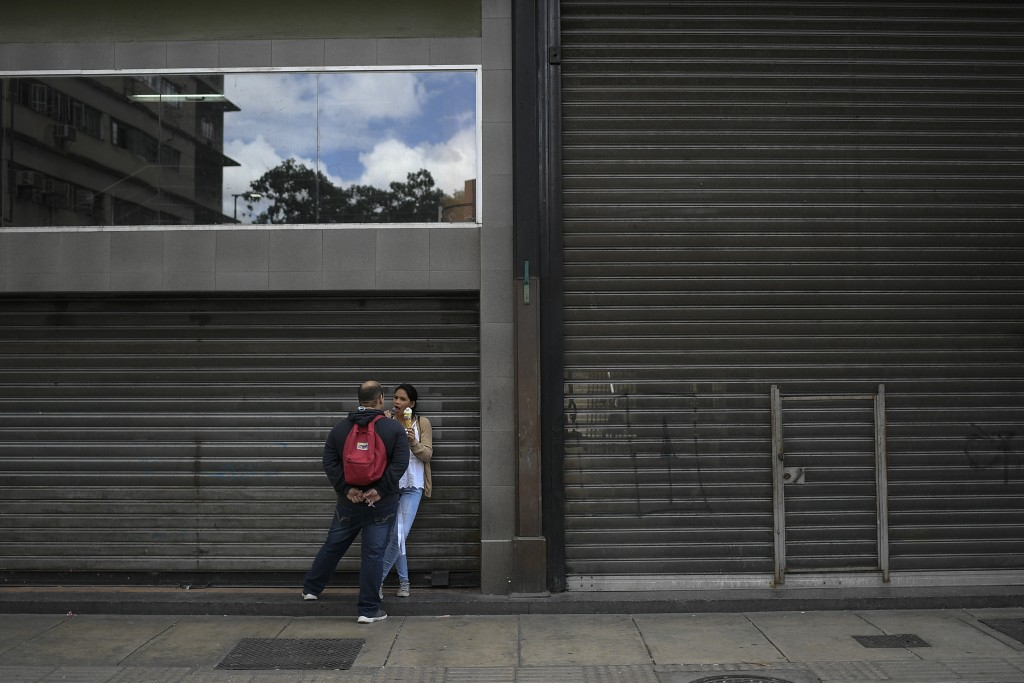 A woman eats ice cream leaning against a shuttered storefront in Caracas, Venezuela, Saturday, July 25, 2020, amid the new coronavirus pandemic. (AP P...