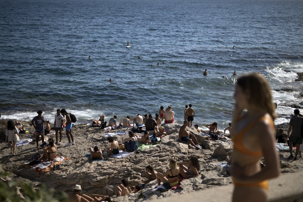 People enjoy the sun at the Malmousque Beach in Marseille, in southern France, Saturday, July 25, 2020. France is reporting a sharp uptick in coronavi...