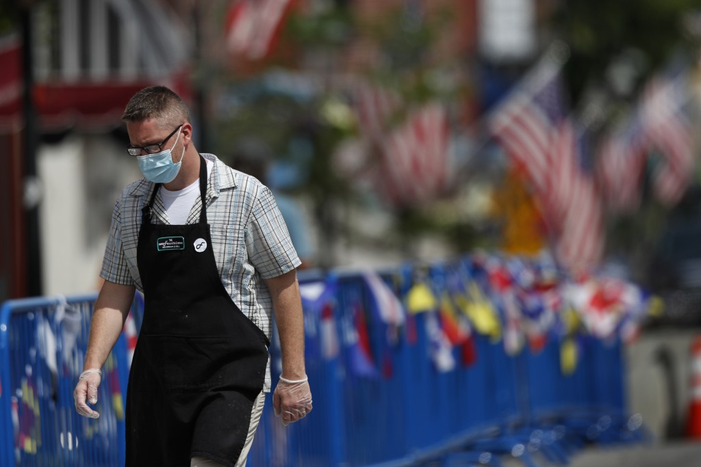 An ice cream shop employee wears a mask to protect against coronavirus while walking to work, Saturday, July 25, 2020, in Bath, Maine. (AP Photo/Rober...