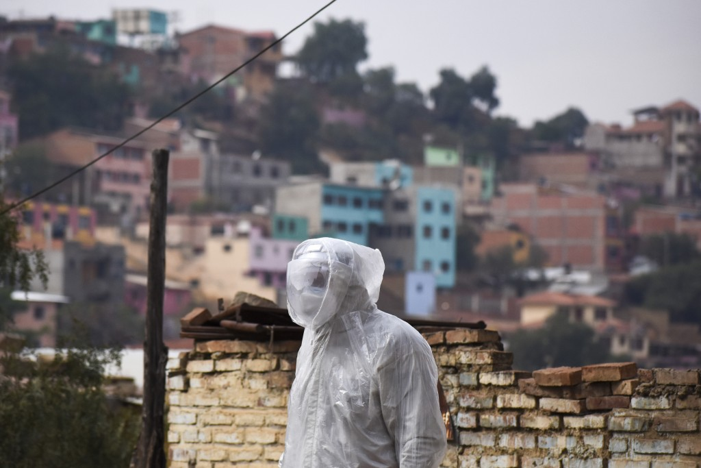 A state department health worker stands in full protective gear while recovering the body of a street vendor who was found at dawn by his neighbors in...