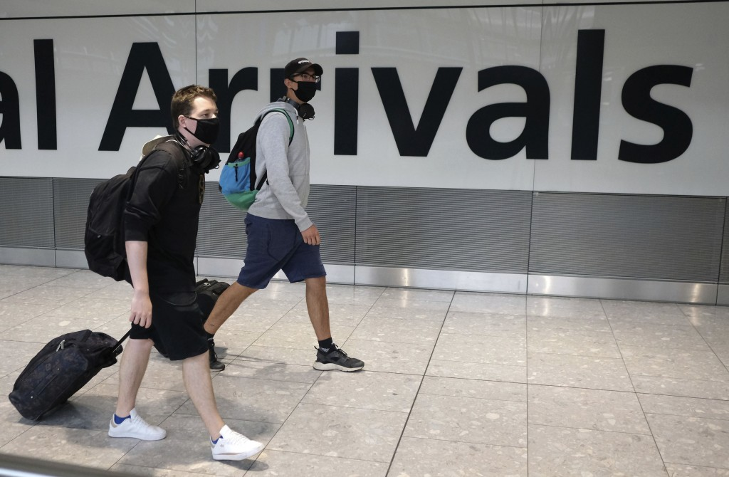 Passengers arrive at Heathrow Airport, in London, Sunday July 26, 2020.  The British government has announced 14-day quarantine restrictions from Sund...