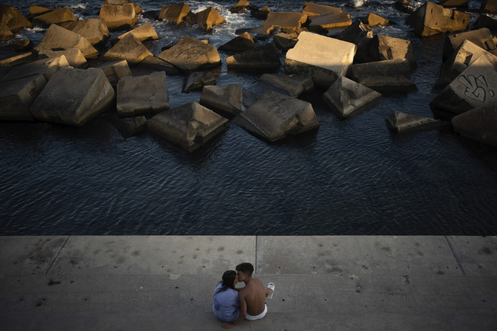 A couple kisses as they sit by the sea in Barcelona, Spain, Saturday, July 25, 2020. Britain is advising people not to travel to Spain and has removed...
