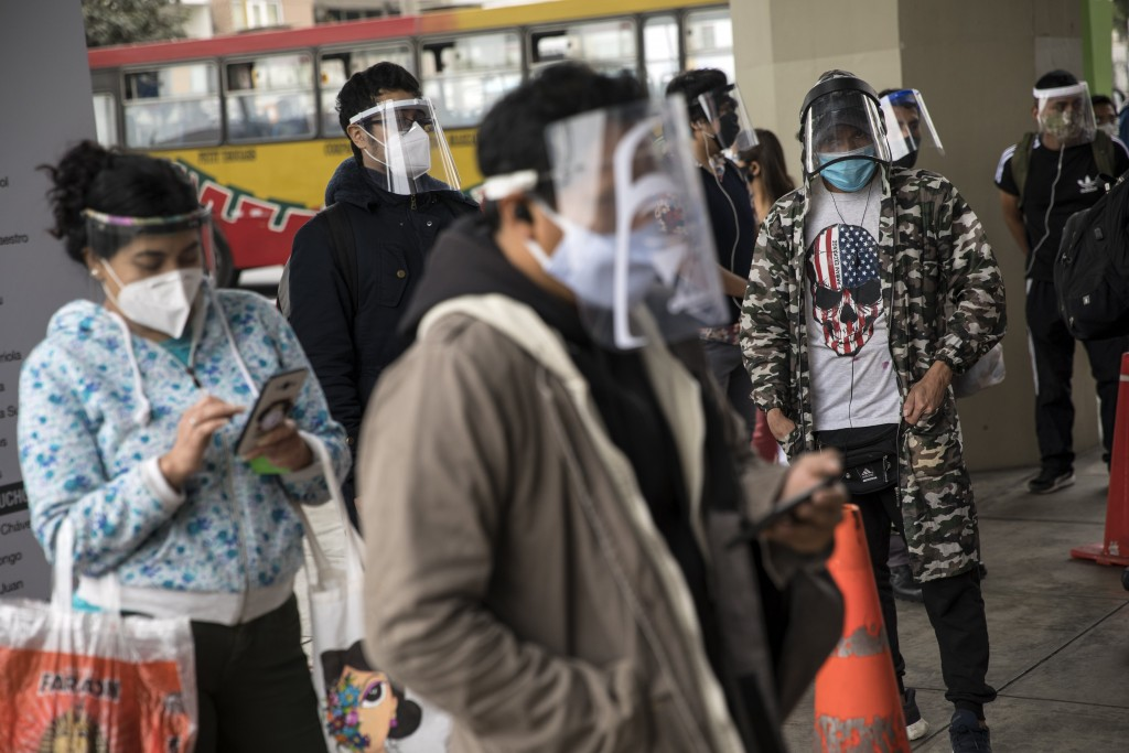 Commuters wearing protective face masks and face shields wait to enter a train station in Lima, Peru, Saturday, July 25, 2020. Peru ordered the mandat...