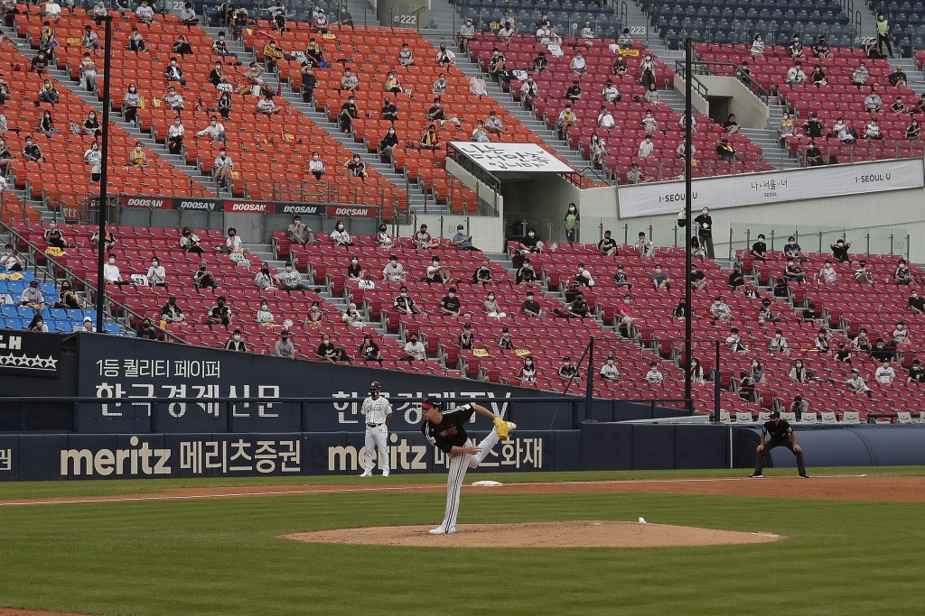 Fans wearing face masks to help protect against the spread of the new coronavirus watch the KBO league game between Doosan Bears and LG Twins in Seoul...