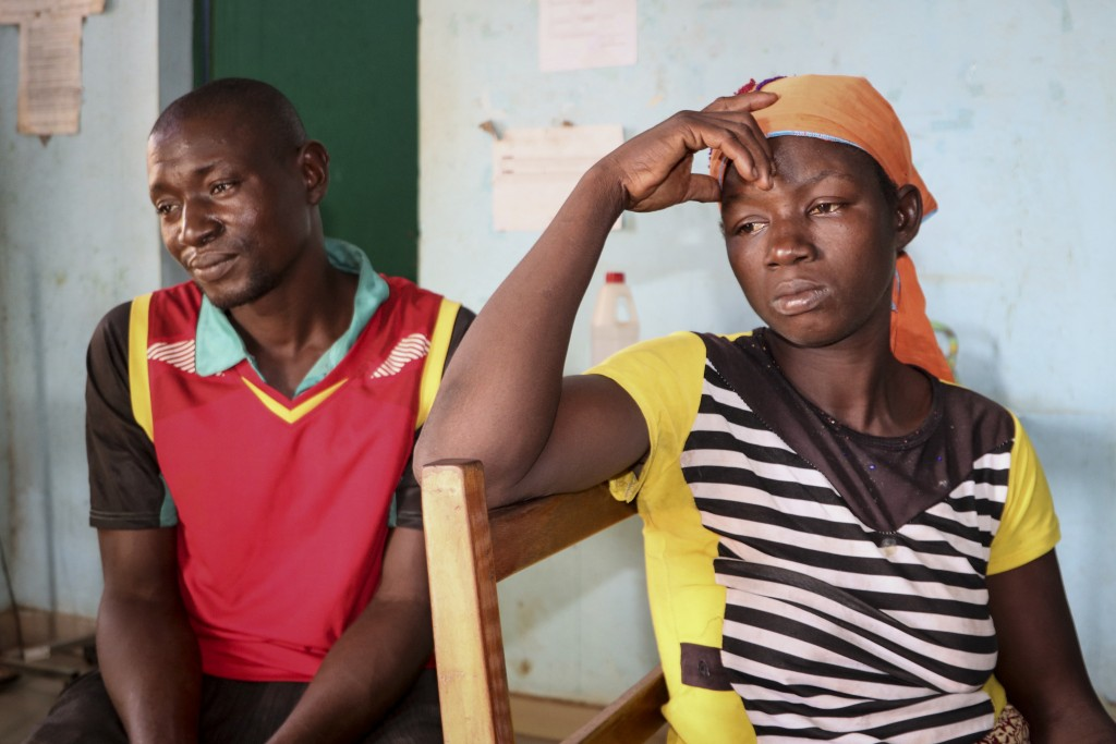 Danssanin Lanizou, 30, right, sits with her husband, Yakouaran Boue, as their one-month old daughter, Haboue Solange Boue, receives medical treatment ...