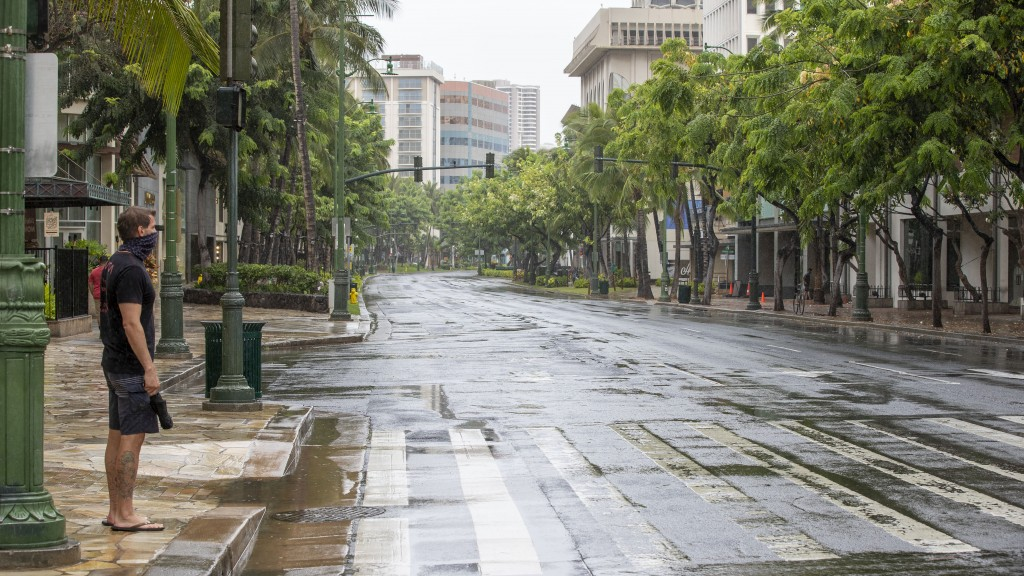 An Oahu resident waits to cross Kalakaua Ave. in a deserted Waikiki, Sunday, July 26, 2020, in Honolulu. Most of Oahu residents are taking shelter and...