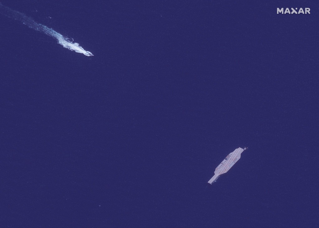 In this July 26, 2020, satellite photo provided on July 27, by Maxar Technologies, an Iranian fast boat, top left, approaches a mockup aircraft carrie...
