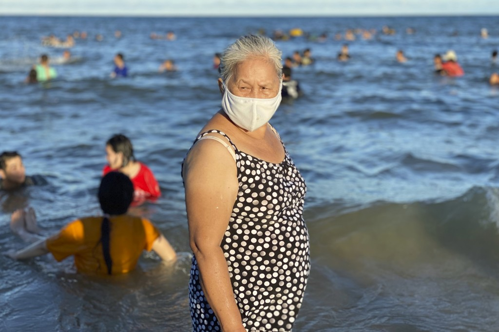 A woman wearing a face mask stands on a beach in Vung Tau city, Vietnam, Sunday, July 26, 2020. Vietnam on Sunday reimposed restrictions in one of its...