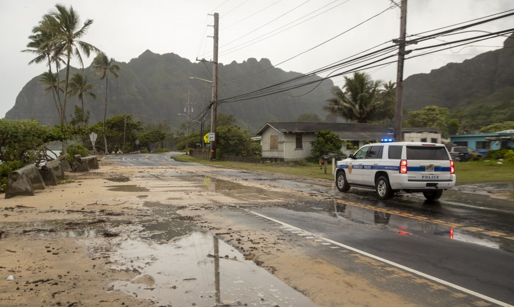 A police officer with the Honolulu Police Department inspects the sand and debris washed onto a closed portion of Kamehameha Highway, Sunday, July 26,...