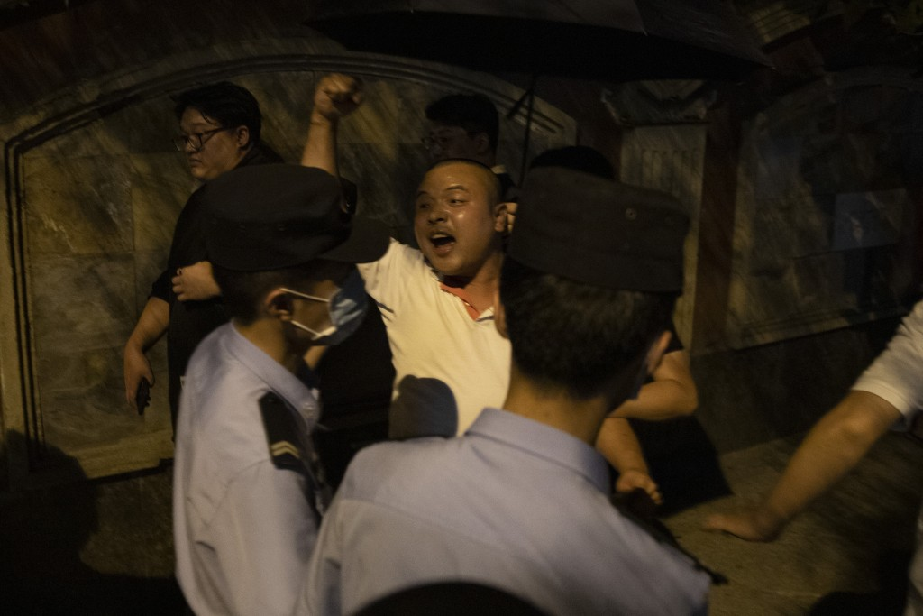 A Chinese man shouts pro-China slogans outside the United States Consulate in Chengdu in southwest China's Sichuan province on Sunday, July 26, 2020. ...