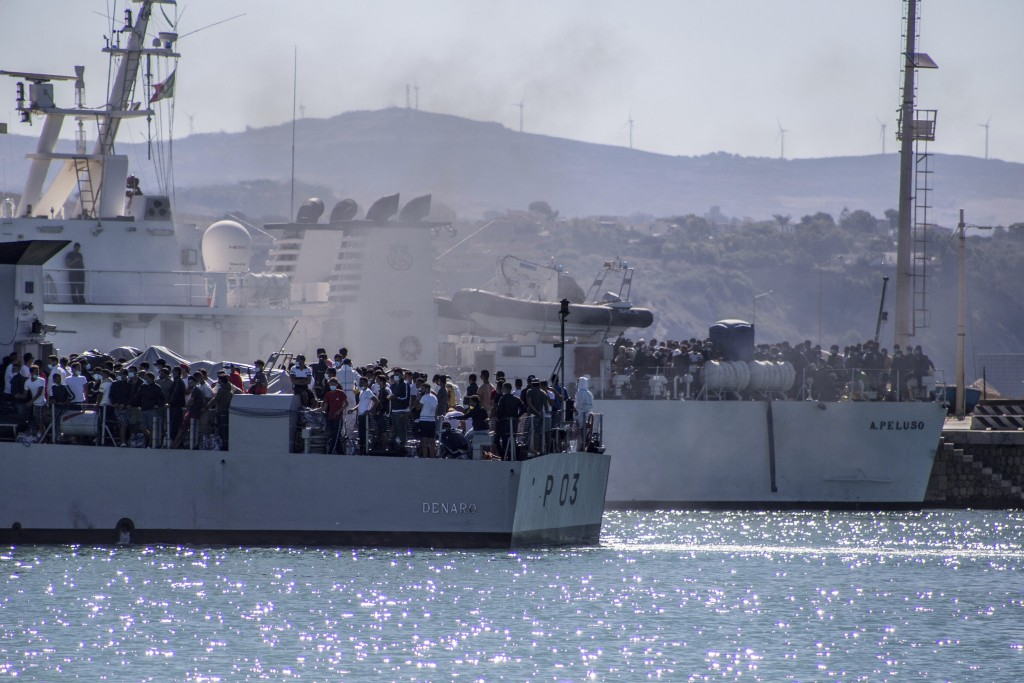 Migrants arrive in Porto Empedocle, Sicily, aboard two military ships after being transferred from the island of Lampedusa, where a number of small bo...