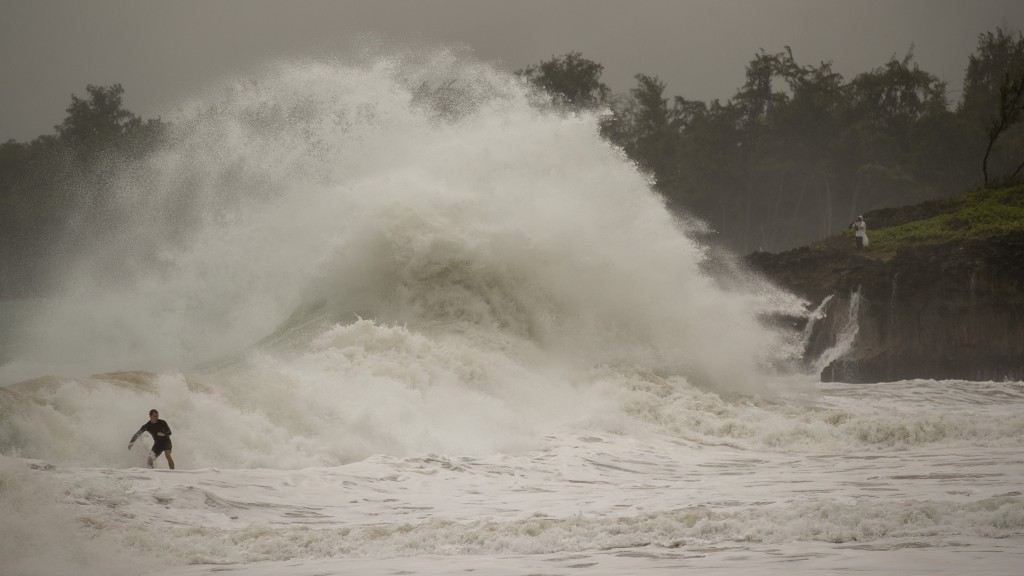 A surfer takes on a wave generated by Hurricane Douglas at Laie Beach Park, Sunday, July 26, 2020, in Laie, Hawaii. (AP Photo/Eugene Tanner)