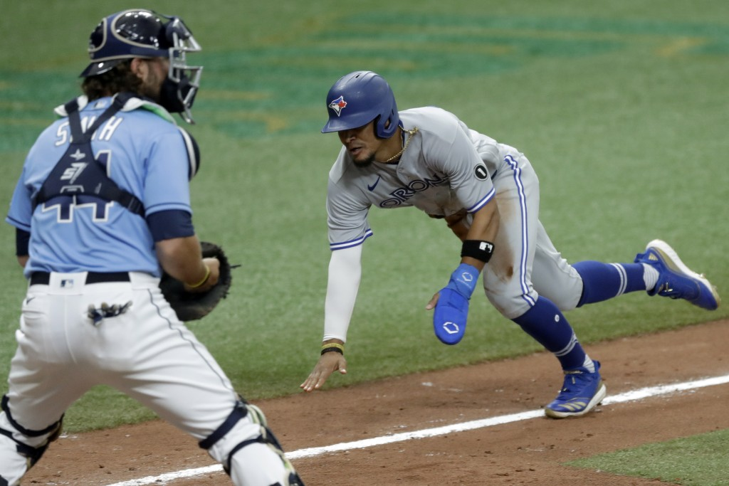 Toronto Blue Jays' Santiago Espinal scores in front of Tampa Bay Rays catcher Kevan Smith (44) on a sacrifice fly by Lourdes Gurriel Jr. during the 10...