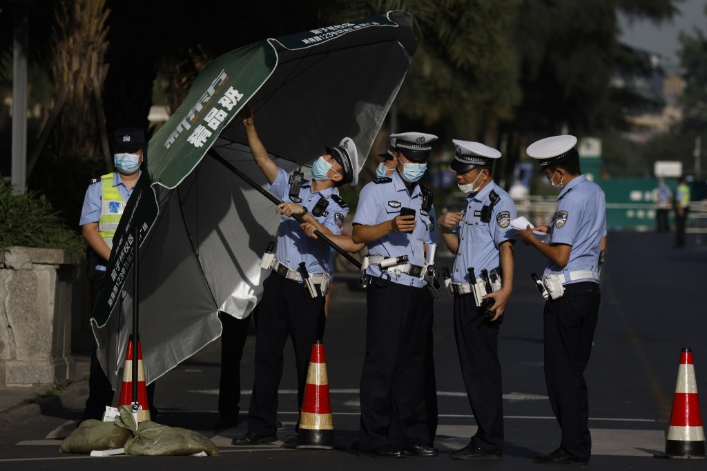 Chinese policemen prepares an umbrella at a checkpoint into the neighborhood of the United States Consulate in Chengdu in southwest China's Sichuan pr...