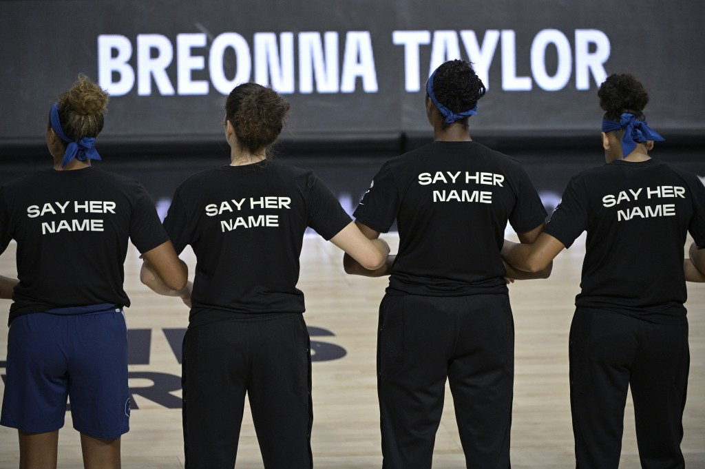 Minnesota Lynx players lock arms during a moment of silence in honor of Breonna Taylor before a WNBA basketball game against the Connecticut Sun, Sund...