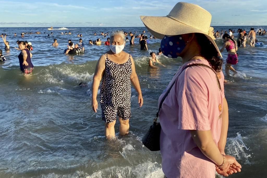 Women wearing face masks stand on a beach in Vung Tau city, Vietnam, Sunday, July 26, 2020. Vietnam on Sunday reimposed restrictions in one of its mos...