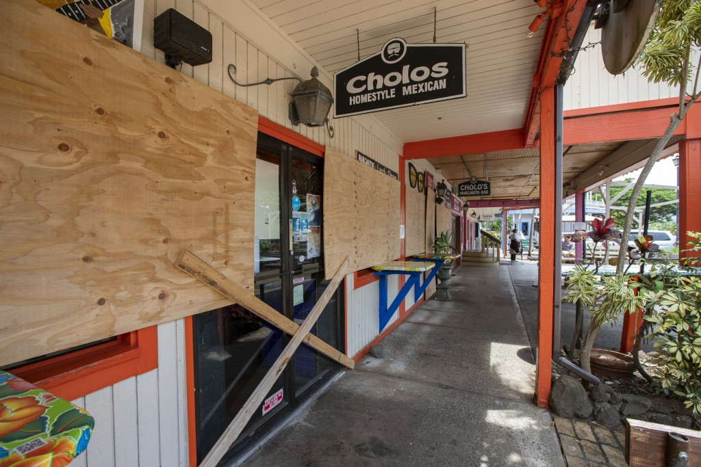 Some businesses in the North Shore Marketplace in Haleiwa, Hawaii, are boarded up and closed in anticipation of Hurricane Douglas, Sunday, July 26, 20...