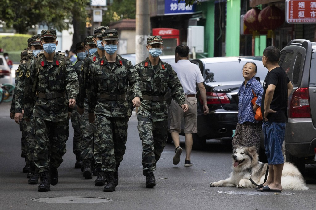Chinese paramilitary policemen march near a neighborhood sealed off before the official closure of the United States Consulate in Chengdu in southwest...