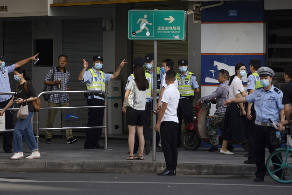 Chinese policemen directs residents away from a neighborhood sealed off before the official closure of the United States Consulate in Chengdu in south...