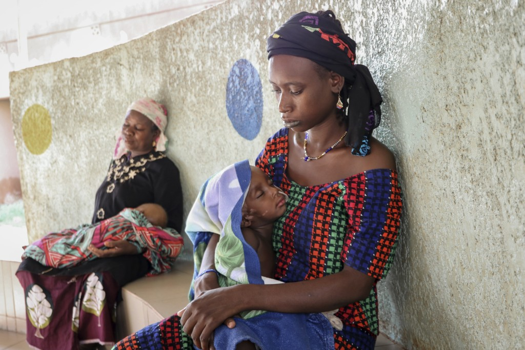 Fatima Li, 20, foreground, holds her two-year-old son, Hama Sow, as he is treated with a feeding tube for malnourishment, as Hadiara Ouedraogo, left, ...