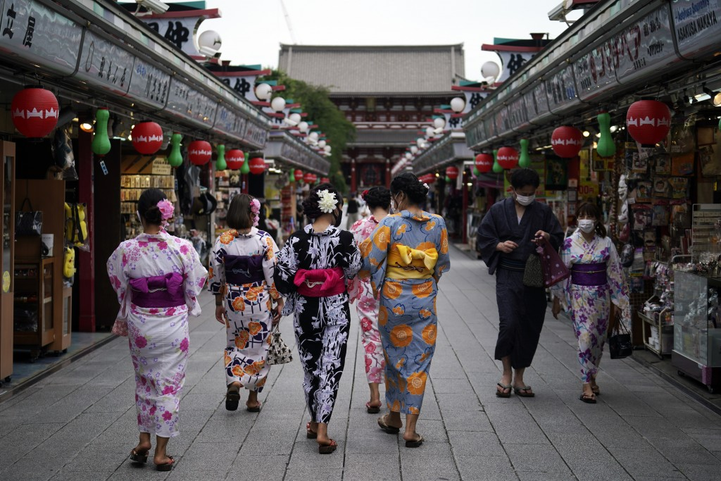 FILE - In this July 27, 2020, file photo, tourists in traditional Japanese kimonos walk in Asakusa district in Tokyo. Tourism operators across Asia an...