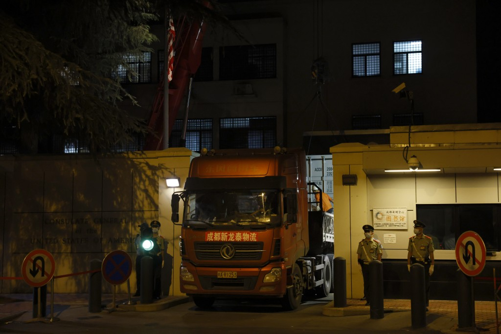 Chinese paramilitary policemen stand and watch, as a container is loaded onto a truck at the entrance to the United States Consulate in Chengdu in sou...