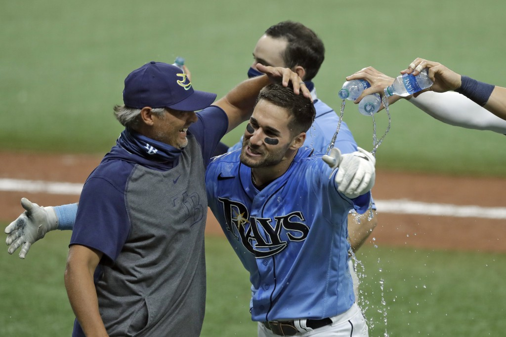 CORRECTS TO TRIPLE, INSTEAD OF DOUBLE - Tampa Bay Rays' Kevin Kiermaier, right, hugs manager Kevin Cash after Kiermaier hit a two-run walkoff triple o...
