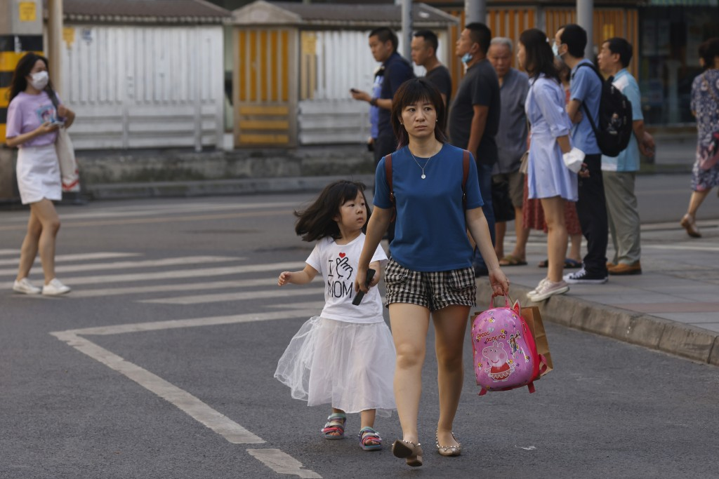 Residents pass by a neighborhood sealed off before the official closure of the United States Consulate in Chengdu in southwest China's Sichuan provinc...