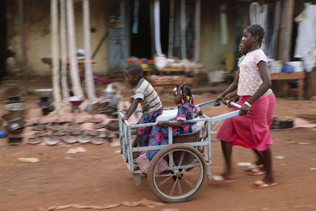 Girls push children in a cart near the market in the town of Hounde, Tuy Province, in southwestern Burkina Faso on Thursday, June 11, 2020. (AP Photo/...