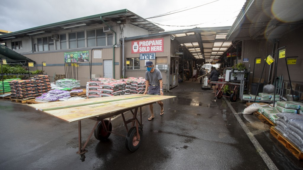 An Oahu resident purchases plywood at the local City Mill hardware store to cover up the windows of his home, Sunday, July 26, 2020, in Honolulu. Oahu...