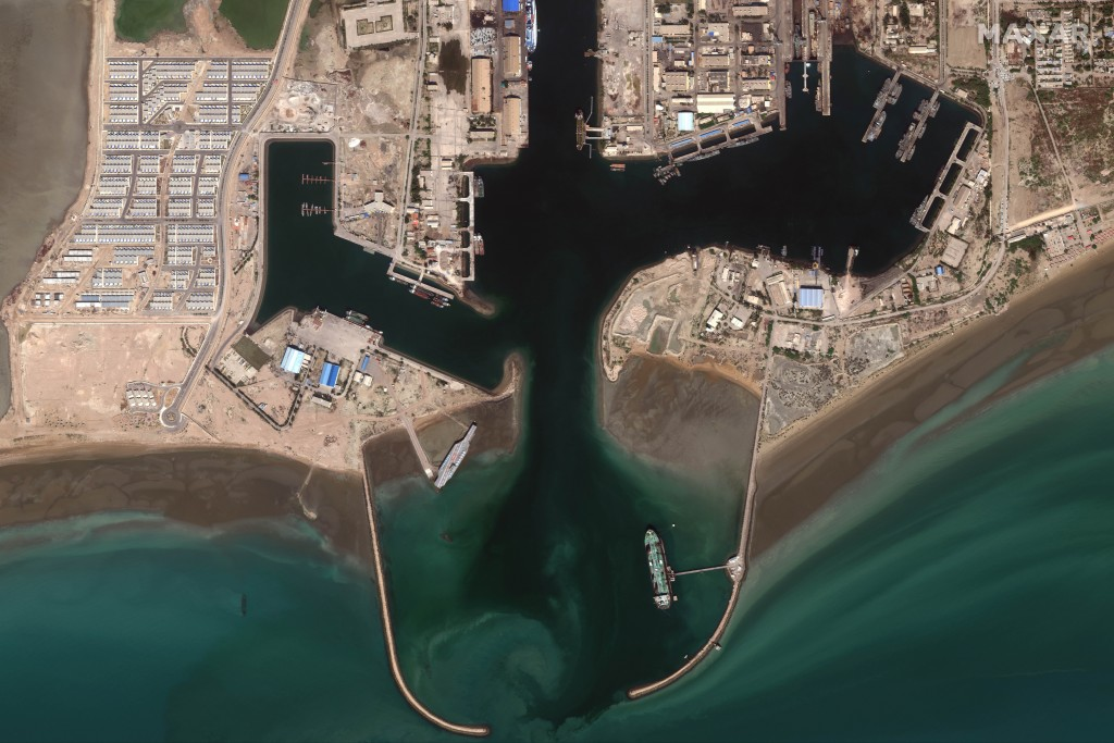 In this Feb. 15, 2020, satellite photo provided on July 27, 2020, by Maxar Technologies, a mockup aircraft carrier, center left, built by Iran is seen...